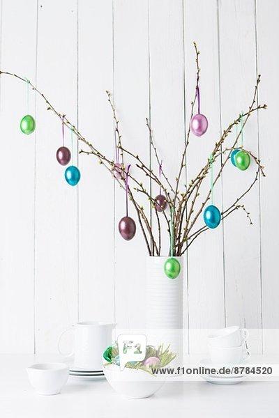 Stilleben von Geschirr und glänzenden Ostereiern  die an Zweigen hängen