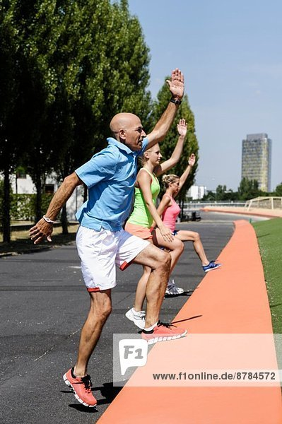 Two young women and trainer exercising in park