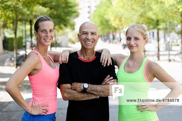 Portrait von zwei jungen Frauen und Trainerin im Park