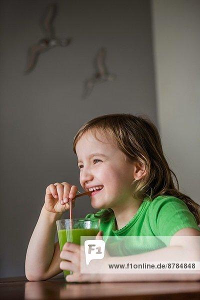 Mädchen trinkt ein Glas Gemüsesaft mit Strohhalm