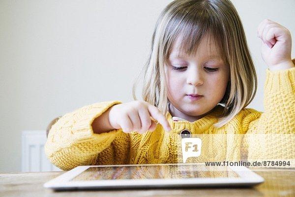 Junges Mädchen am Küchentisch mit digitalem Tablett