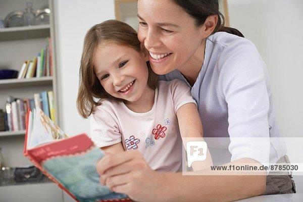 Mutter und kleine Tochter beim Lesen des Märchenbuches