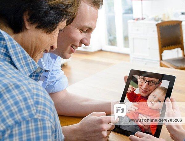 Seniorin und junger Mann beim Betrachten des Bildes von Vater und Sohn auf digitalem Tablett