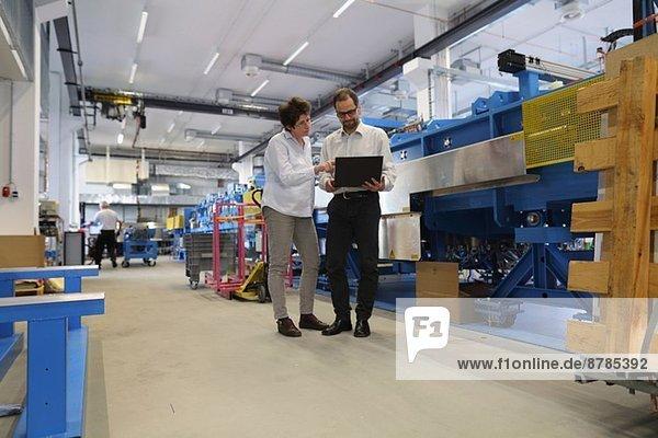 Manager und Arbeitskollege prüfen Informationen auf dem Laptop