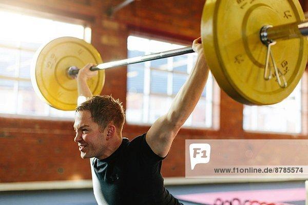 Mann hebt Gewichte in der Turnhalle