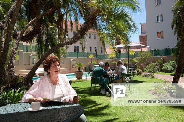 Seniorin beim Kaffee im Garten der Seniorenvilla