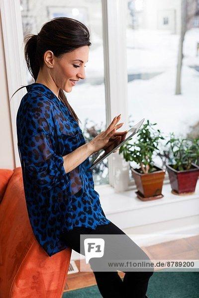 Junge Frau im Wohnzimmer mit digitalem Tablett