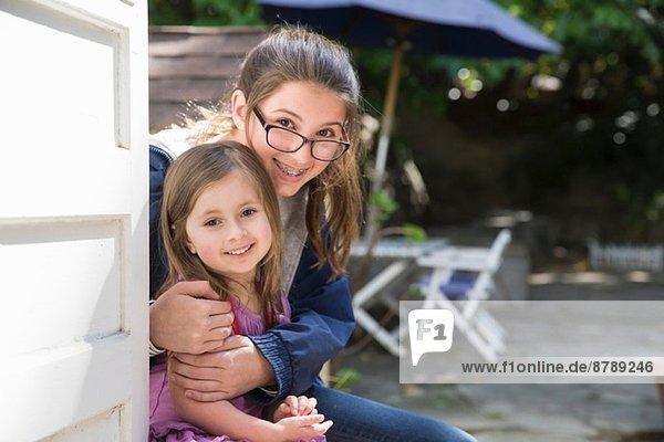 Mädchen umarmende Schwester im Garten