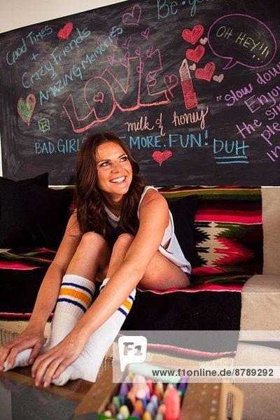 Junge Frau auf Sofa sitzend mit Socken