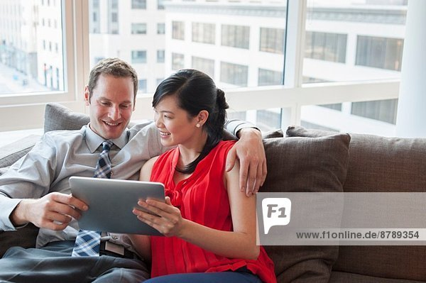 Paar Entspannung auf dem Sofa mit digitalem Tablett