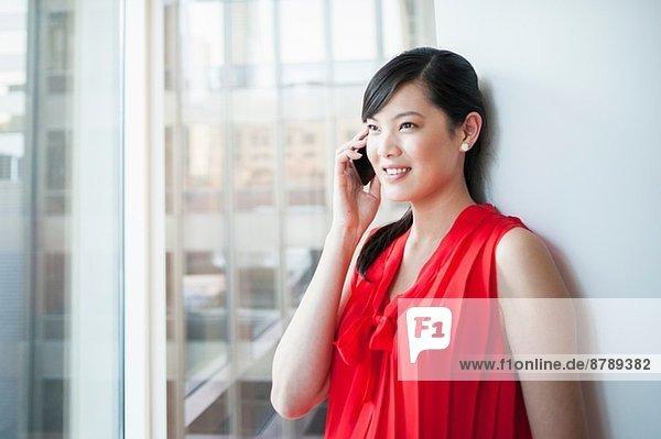 Junge Geschäftsfrau beim Telefonieren im Büro
