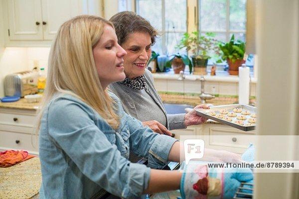 Seniorin und Enkelin backen Kekse im Ofen