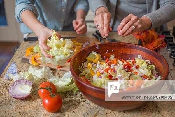 Senior woman and granddaughter chopping vegetables for salad