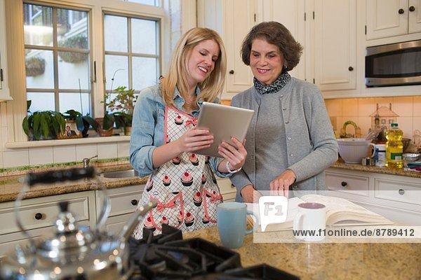 Seniorin und Enkelin prüfen Rezept auf digitalem Tablett