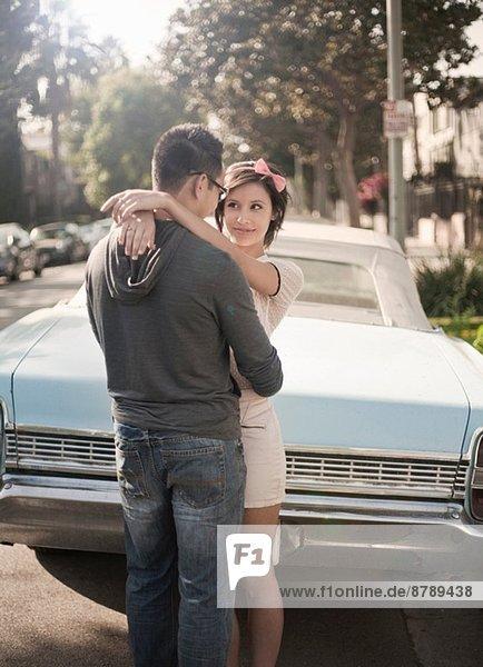 Paar umarmt neben dem Cabriolet