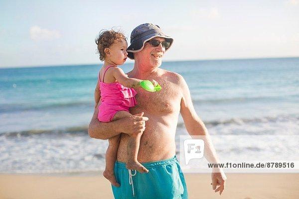 Großvater und Enkelin am Strand