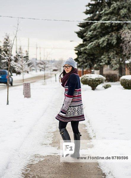 Junge Frau geht die schneebedeckte Straße hinunter