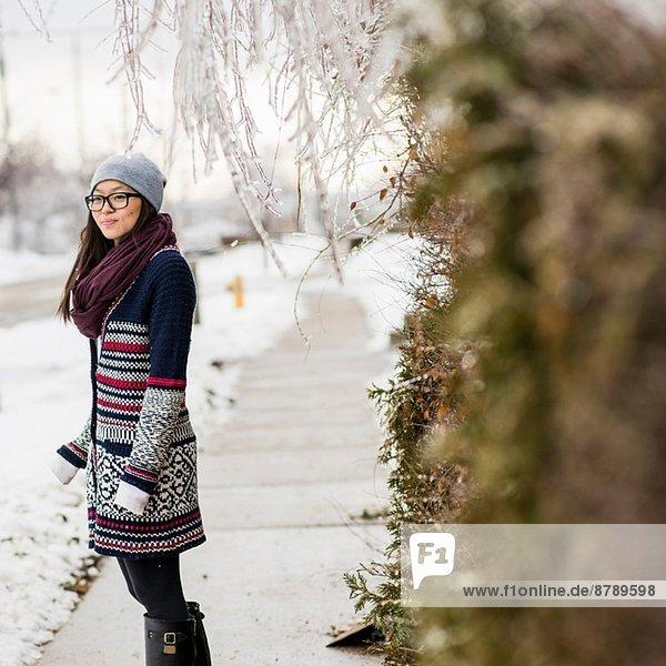 Junge Frau auf eisbedeckter Straße stehend