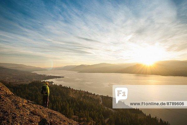 Männlicher Wanderer bei Sonnenuntergang über dem Okanagan Lake  Naramata  British Columbia  Kanada
