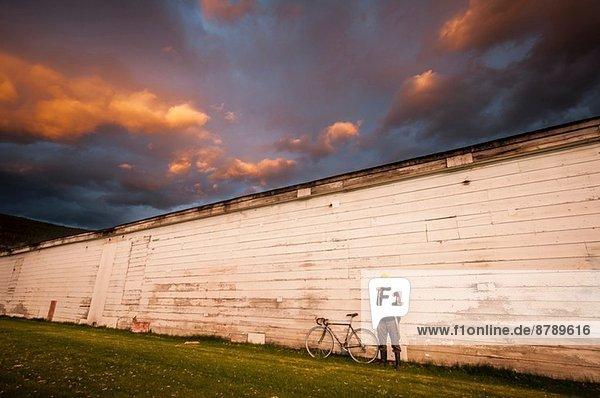 Junger Mann  der mit dem Fahrrad an der weißen Wand steht.