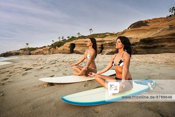 Zwei Surfer  auf Surfbrettern am Strand sitzend  meditierend