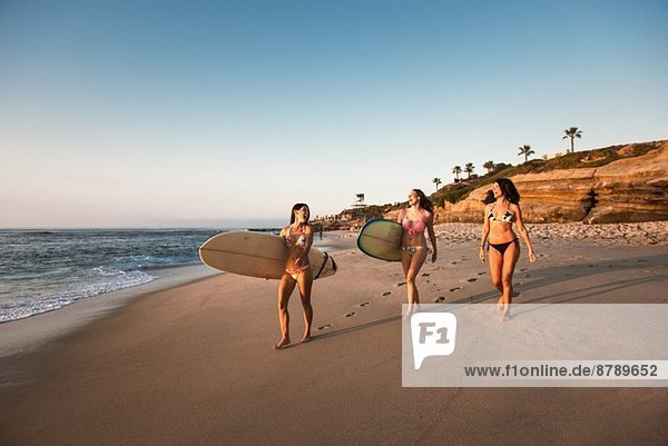 Surfers carrying surf boards  walking along beach