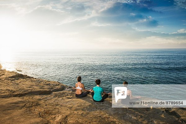 Women sitting on cliff top  looking at sea and meditating