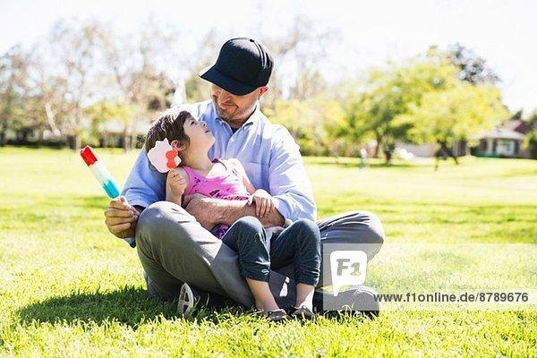 Mittlerer Erwachsener Mann und Tochter essen Eislutscher im Park