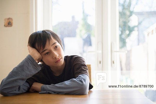 Boy sitting at table  head resting in hand