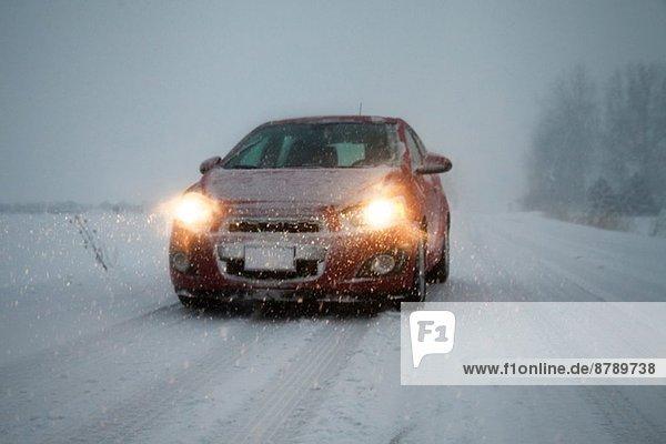 Auto mit Scheinwerfern auf nebliger  schneebedeckter Fahrbahn