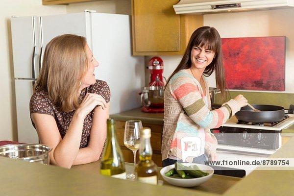 Mittlere erwachsene weibliche Freunde  die Essen in der Küche zubereiten.
