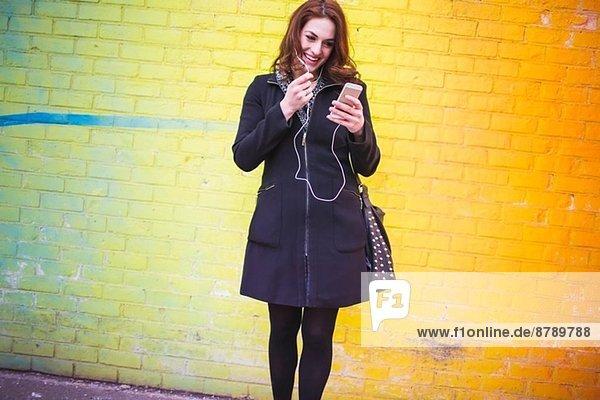 Junge Frau wählt Musik auf der Stadtstraße