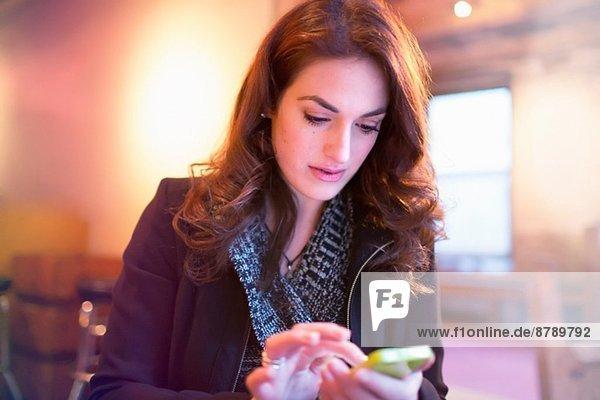 Junge Frau beim SMSen auf dem Smartphone im Cafe