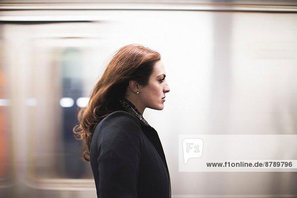 Junge Frau pendelt in der U-Bahn