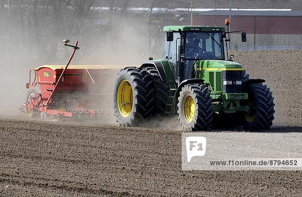 Traktor mit Sämaschine bei der Arbeit auf einem Feld im Frühjahr  Köpingebro  Schonen  Schweden