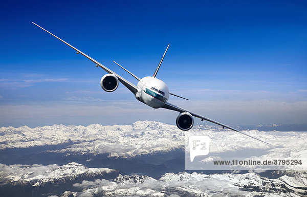 Cathay Pacific Boeing 777-367 ER in flight over mountains