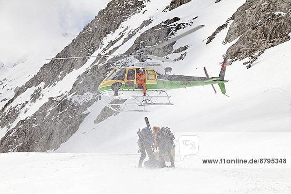 Helikopter setzt zur Landung auf dem Cavardiras-Gletscher an  um Menschen ins Tal zu fliegen  Graubünden  Schweiz