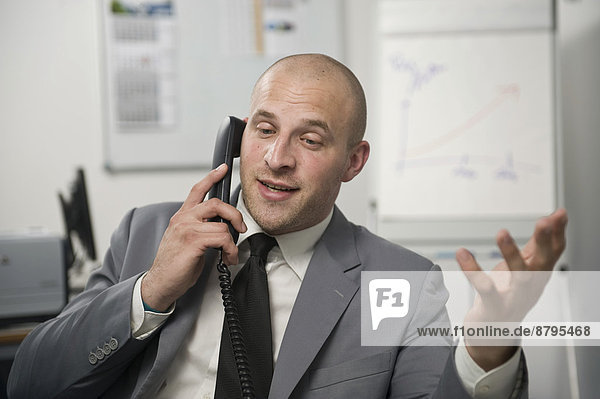 Young man wearing a suit is talking on a phone in the office