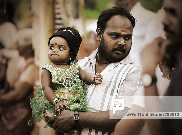 Father holding a child at a temple festival  Kerala  South India  India