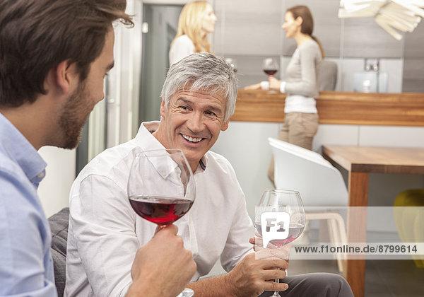 Zwei Männer mit Weinglas  im Hintergrund zwei Frauen mit Weinglas