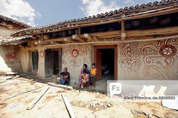Außenaufnahme sitzend Wohnhaus streichen streicht streichend anstreichen anstreichend Volksstamm Stamm Indien Schlamm