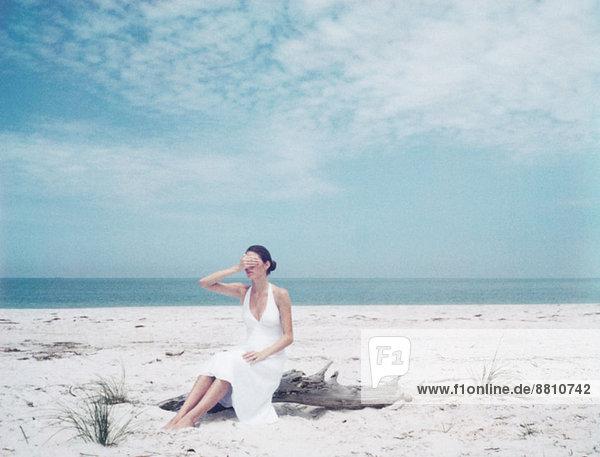 Frau auf Treibholz am Strand sitzend  die Augen mit der Hand bedeckend