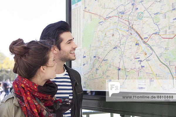Touristenpaar schaut sich den Stadtplan an der Touristeninformation an. Touristenpaar schaut sich den Stadtplan an der Touristeninformation an.