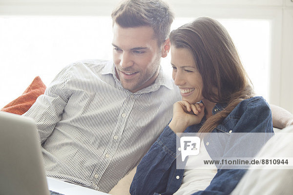 Couple relaxing at home looking at laptop computer together
