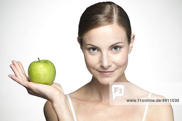 Junge Frau hält grünen Apfel hoch