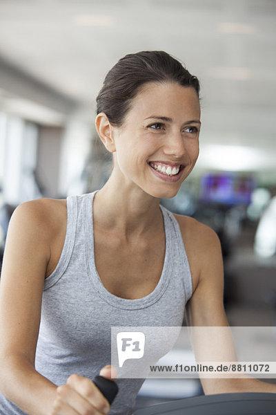 Junge Frau mit Stepperin im Fitnessstudio