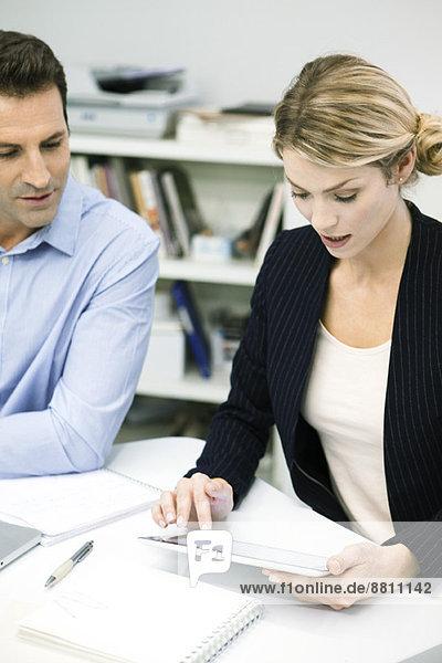 Kollegen schauen auf das digitale Tablett herab