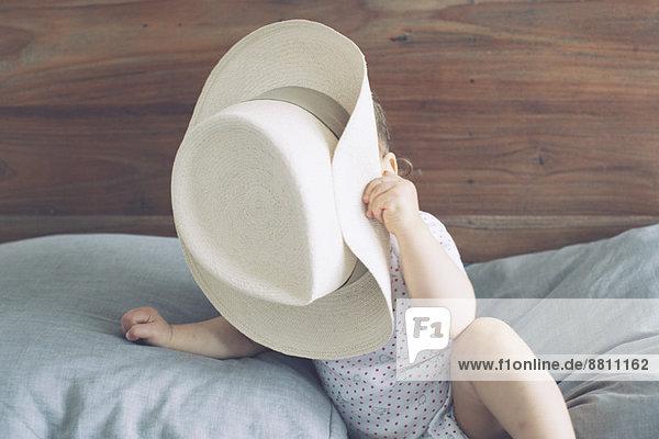 Baby mit Gesicht  das von einem übergroßen Hut verdeckt wird. Baby mit Gesicht, das von einem übergroßen Hut verdeckt wird.