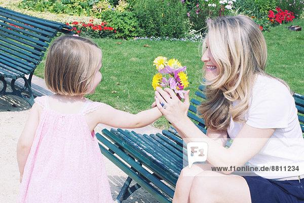 Kleines Mädchen präsentiert Mutter mit Blumenstrauß