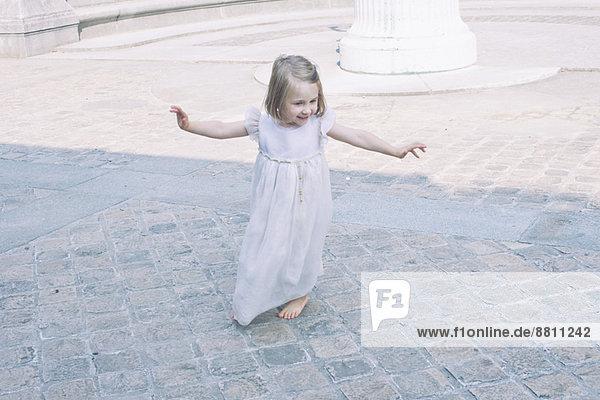 Kleines Mädchen mit ausgestreckten Armen beim Spielen im Freien